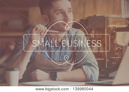 Business strategy. Inspirational typographic poster for small business with young man in background planning new business
