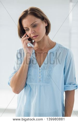 Young woman talking on mobile phone at home