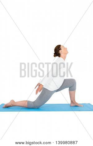 Side view of woman exercising on while background