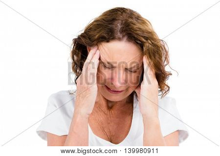 Close-up of mature woman with head in hands while standing on white background