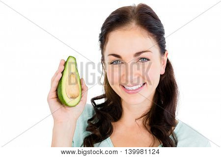 Portrait of happy woman holding avocado against white background