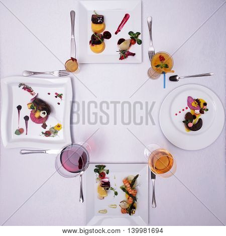 Food and drink restaurant. Desserts and drinks symmetrically served on white table.