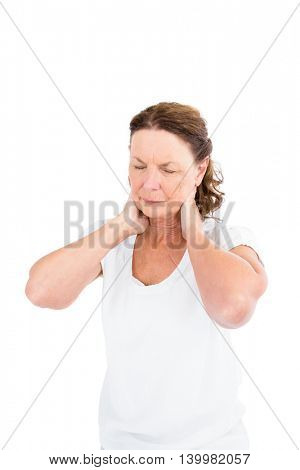 Mature woman suffering from neck pain while standing against white background