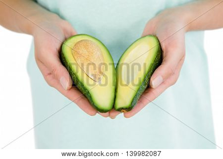 Midsection of woman holding avocado slices