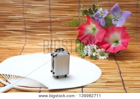 Suitcase, fan and morning glory on bamboo blind. Concept of travel in Japanese summer.