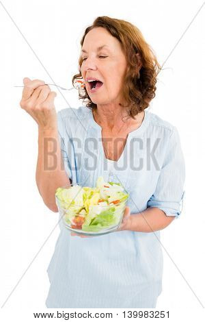 Mature woman having vegetable salad while standing against white background