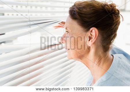 Close-up of mature woman looking through blinds
