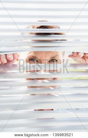 Close-up portrait of mature woman looking through blinds