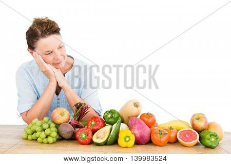 Thoughtful woman standing by fruits and vegetables at table on white background