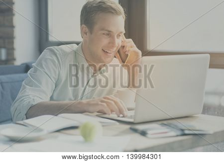 Connection. Young smiling and cheerful man talking on smart phone and using laptop being in the office during his working day