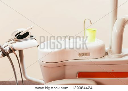 Dental chair components: ceramic spittoon water filler and assistant tool rack in a modern dentist office.