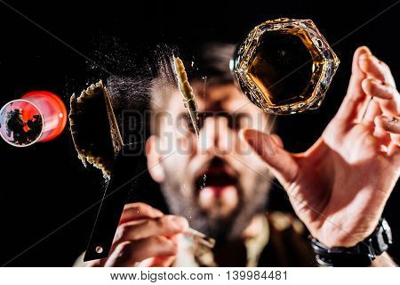Man preparing a shot for snorting or sniffing cocaine lines on mirror with rolled banknote
