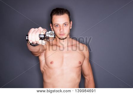 Blurry pose of a shirtless fit man pointing a gun to the camera. Focus on the gun