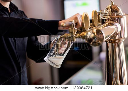 Midsection of bartender pouring beer from faucet in pint glass at bar