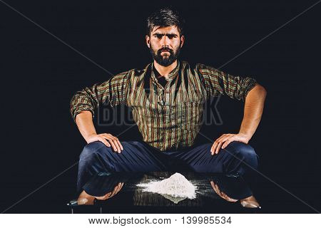 Man being confident near a table with cocaine