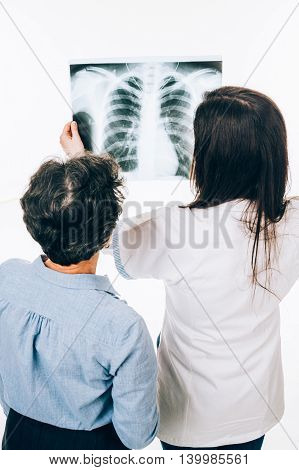 Back of female doctor and senior patient while looking at lung radiography - isolated on white
