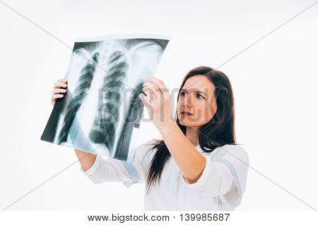 Young female doctor is examining lung radiography with attention - isolated on white
