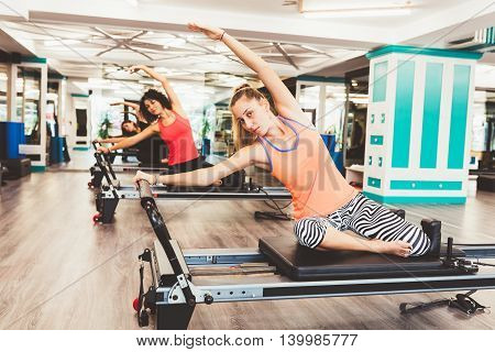 View of women exercising on reformer bed at gym