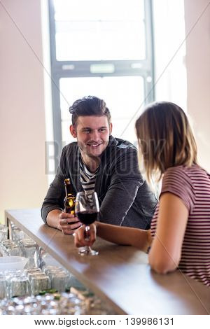 Happy young man with girlfriend at counter in bar