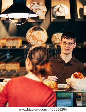 Skilled salesman is serving his customer in a bakery.