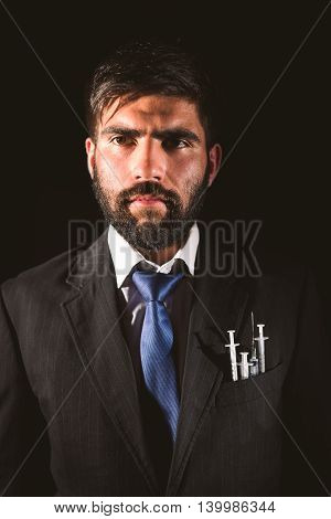 Portrait of a man wearing a suit with syringes on it's pocket