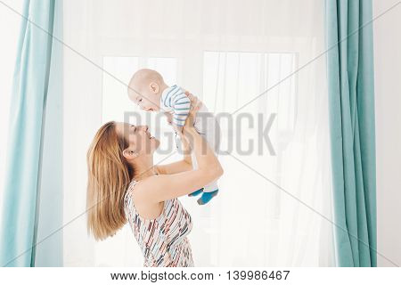 Fulfilled young mother holding her baby boy in arms