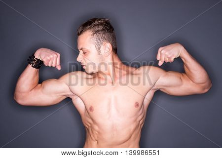 Bearded muscular man looking at his tense biceps