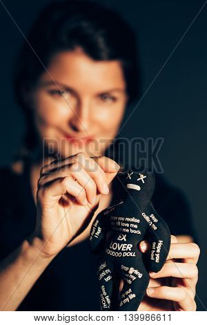 Smiling woman stabbing a voodoo doll with a needle