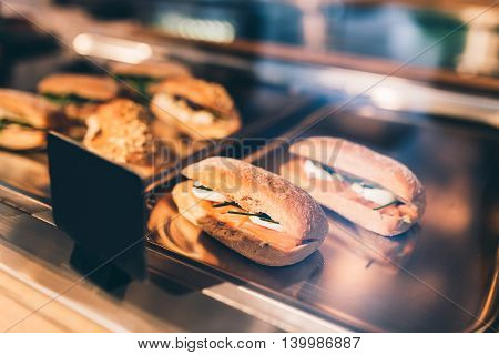 Fresh tasty sandwiches with salmon eggs and herbs on a tray in a pastry