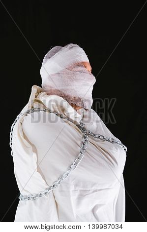 Profile of an insane man with straitjacket bandages on his face and chains around him