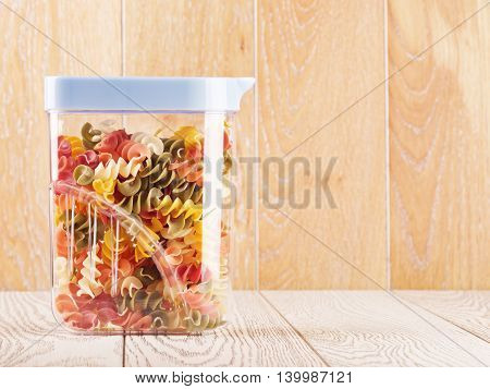 raw spiral pasta of different color in plastic container