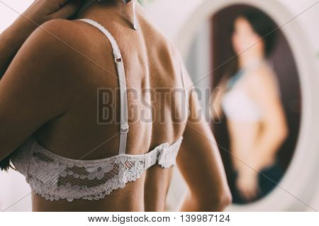Woman in a sexy white bra in front of the mirror blurred image