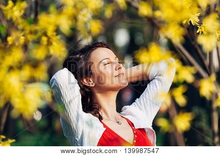Carefree smiling woman behind leafs with arms holding her hair looking at the sun