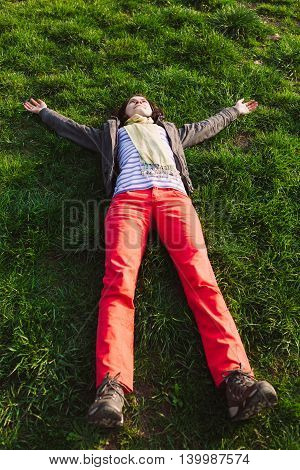 Woman raising arms enjoying freshness of spring season while lying on grass