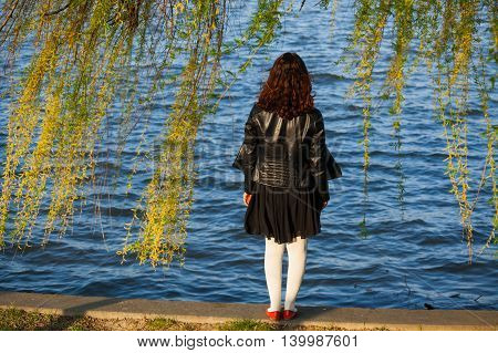 Back of a brunette woman standing on the edge of a lake and looking away