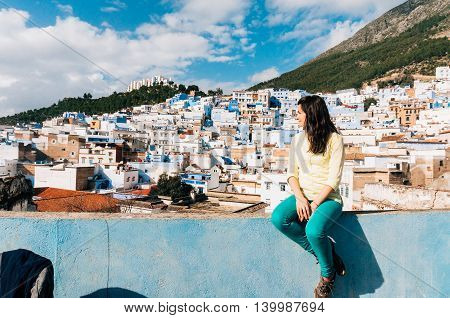 Beautiful female tourist is looking from above at Chefchaouen blue small city in Morocco