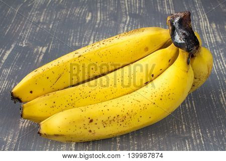 Bunch of yellow bananas on wooden surface