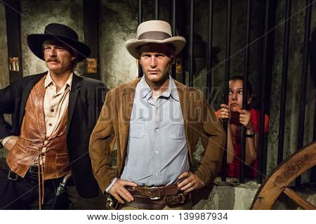 Los Angeles CA USA - July 6 2013: Madame Tussaud's Hollywood figures - female tourist in jail behind Robert Redford and Paul Newman.