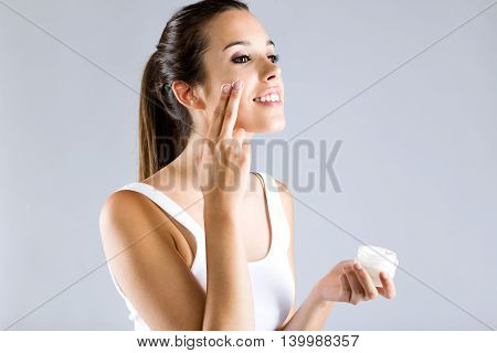 Pretty Young Woman Applying Body Cream. Isolated On Gray Background.