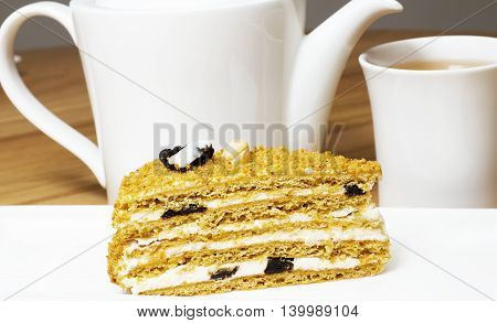 Traditional honey cake on plate and white cup of tea on table