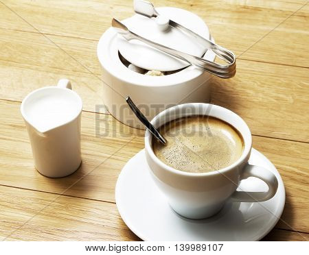Coffee Cup of Coffee with Milk Jug on Wood Background