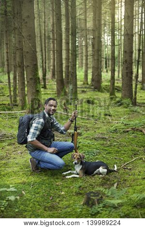 Interracial hunter with his dog in the forest aiming at prey
