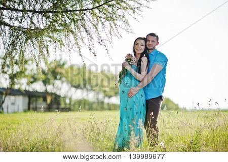 Happy Pregnant Couple At Turquoise Dress On The Garden