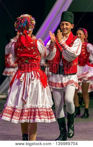 ROMANIA TIMISOARA - JULY 7 2016: Young Romanian dancers in traditional costume perform folk dance during