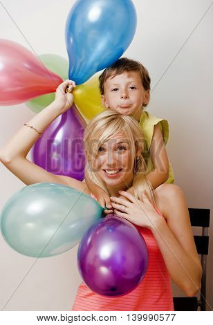pretty real family with color balloons on white background, blond woman with little boy at birthday party bright smiling happy mother