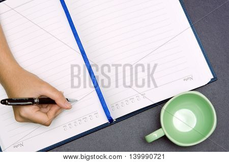 A girl hand is holding a pen and writing on a book with a cup