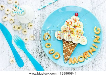 Pancakes with banana in the form of ice cream for children fun breakfast. Good morning concept