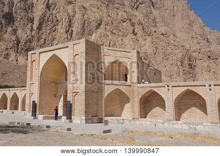 Lonely tourist standing at entrance of stone caravanserai structure ancient hotel building in Kermanshah, Iran
