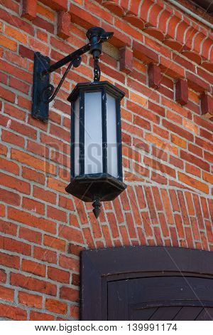 Suspended lantern on a brick wall retro.