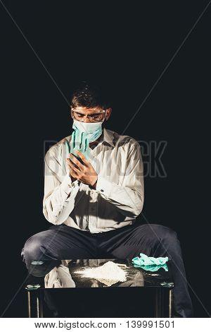 Drug dealer putting on gloves for cocaine preparation